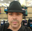 [ Photo of Christian Fernandez. He is wearing a black, brimmed hat, a black shirt, and stands in a store. ]