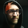 [ Photo of Gordon Hall. He has large glasses, dyed orange hair, and is wearing a grey sweatshirt with the hood pulled up. ]