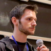 [ Photo of Mike Gerwitz. He is standing in front of a black board, giving a talk. ]