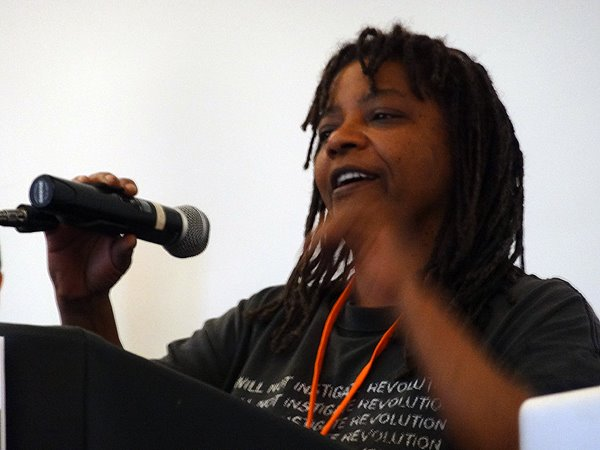 [ Photo of Micky Metts. She is wearing a black shirt and giving a talk at a podium. ]