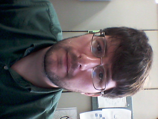 [ Photo of Andrew Seeder. He is sitting in an office, wearing a green shirt with a collar. ]